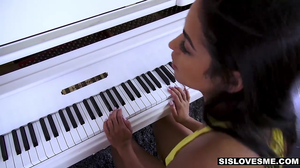 Exotic teen brunette gives a handjob by the piano